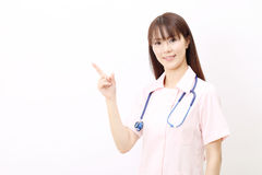 Young asian female nurse. Pointing Royalty Free Stock Photo