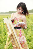 Young Asian female painter. With her oil painting in rape field Royalty Free Stock Photography