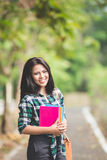 Young asian female student holding books while walking on the pa Stock Photos