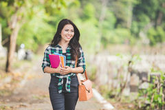 Young asian female student holding books while walking on the pa Royalty Free Stock Photos