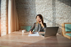 Young Asian  female talking on a cell phone. Beautiful young Asian talking on a cell phone while writing pen on a paper document while sitting in an expensive Royalty Free Stock Photo