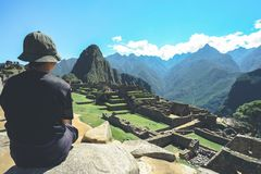A young asian female traveler is admiring the Inca ruins of Machu Picchu, one of the New Seven Wonder of The World. royalty free stock images
