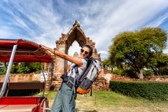 Young asian female traveler with backpack traveling with standing on taxi or Tuk Tuk and happy fun with old temple Wat Mahathat Royalty Free Stock Image