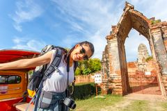 Young asian female traveler with backpack traveling with standing on taxi or Tuk Tuk and happy fun with old temple Wat Mahathat Stock Image