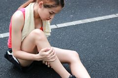Young Asian fitness woman runner suffering from broken legs. Running injury accident concept stock image