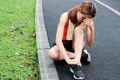 Young Asian fitness woman runner suffering from broken twisted ankle. Running injury accident concept. Young Asian fitness woman runner suffering from broken royalty free stock image