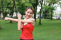 Young Asian fitness woman stretching her hands before run in park. Fitness and exercise concept. Stock Photos