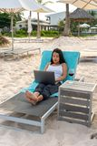 Young Asian freelancer working on laptop at the beach stock photo