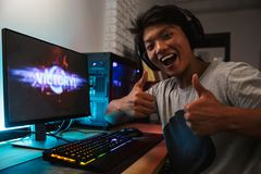 Young asian gamer boy rejoicing victory while playing video game. S on computer in dark room wearing headphones and using backlit colorful keyboard stock images