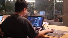 Young Asian Gamer Playing Counter-Strike Game on Computer in Cafe. 4K. Bangkok, Thailand - OCT 26 2017. stock video footage