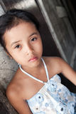 Young Asian girl against wall. Young Philippine girl from impoverished neighborhood against wall Stock Photography
