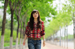 Young Asian girl in alameda. A beautiful Asian girl taking a walk in a pleasantly cool alameda Royalty Free Stock Image