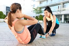 Assiting a friend. Young Asian girl assisting her friend who is doing sit-ups Royalty Free Stock Photography