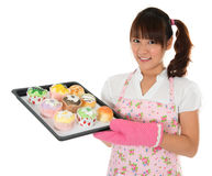 Young Asian girl baking bread and cupcakes. Wearing apron and gloves holding tray isolated on white Stock Photography