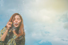 Young asian girl blowing soap bubbles Royalty Free Stock Image