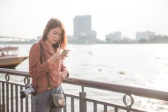 Young asian girl using mobile phone for search interesting places in bangkok. Young asian girl in brown shirt traveling in thailand and using mobile phone for royalty free stock photo