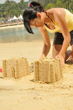 Young Asian Girl Building Sandcastle By The Beach royalty free stock photo