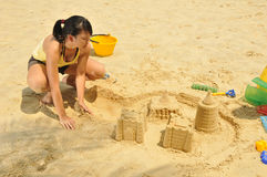 Young Asian Girl Building Sandcastle By The Beach Royalty Free Stock Photography