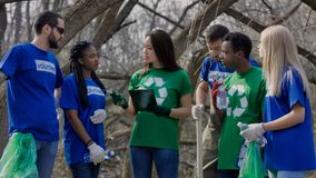 Girl coordinating group of volunteers. Young Asian girl with clipboard coordinating diverse volunteers for work of cleanup in spring forest stock photo
