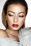 A young Asian girl with creative makeup, arrows and bright red lips with sparkles. A beautiful model with perfect skin in a f. Ur coat made of artificial fur and Stock Photography