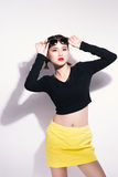 Young asian girl doing emotion. Dressed in a black shirt and yellow skirt, glasses and bright lips,trendy clothes. Stock Photos