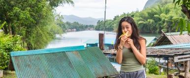 Young Asian girl eating banana stock photography