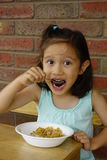 Young Asian Girl Eating Breakfast Cereal. Stock Photos