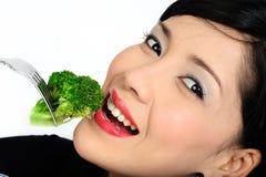 Young asian girl eating broccoli Stock Photo
