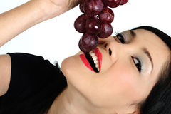 Young asian girl eating grape Stock Photography