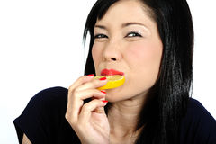 Young asian girl eating lemon Stock Photo