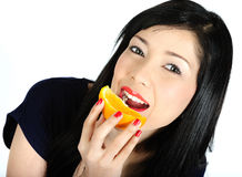 Young asian girl eating orange Stock Photo