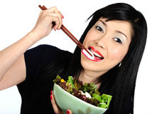 Young asian girl eating salad Royalty Free Stock Images