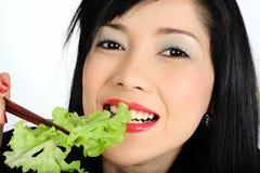 Young asian girl eating salad Stock Photos
