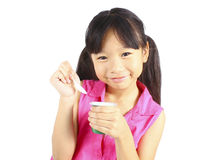 Young asian girl eating yogurt Royalty Free Stock Photography