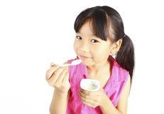 Young asian girl eating yogurt Stock Image