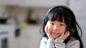 A young asian girl enjoying listening to music on her headphone stock video