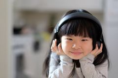 A young asian girl enjoying listening to music on her headphone stock photo
