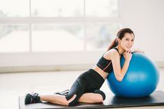 Young Asian girl exercise at clean home gym, sports club. Rest on fitness ball. Yoga aerobic class, sport trainer concept royalty free stock image