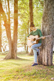 Young asian girl in forest with guitar Royalty Free Stock Photos