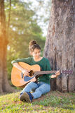 Young asian girl in forest with guitar Royalty Free Stock Image