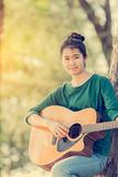 Young asian girl in forest playing guitar Stock Photos
