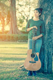 Young asian girl in forest playing guitar Royalty Free Stock Image