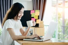 Young asian girl is freelancer with her private busines. S at home office, working with laptop, coffee, online marketing, Customer order and packaging or packing Royalty Free Stock Photo