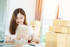 Young asian girl is freelancer with her private business at home office. Working with laptop, coffee, online marketing, Customer order and packaging or packing Royalty Free Stock Image