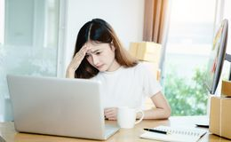 Young asian girl is freelancer with her private business at home office. Working with laptop, coffee, online marketing, She was worried that the sales slump/ Stock Images