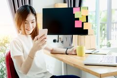 Young asian girl is freelancer with her private business. At home office, working with laptop, coffee, online marketing, Customer order and packaging or packing Royalty Free Stock Photography