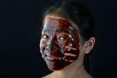 Young asian girl having fun with a chocolate mask stock photo