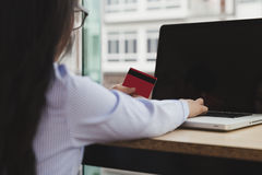 Young asian girl holding credit card on laptop for internet onli Stock Photos