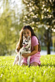 Young Asian girl hugging puppy sitting on grass Stock Images