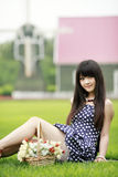 Young Asian girl on the lawn. Young Asian girl with a basket of flowers sitting on the lawn Stock Photos